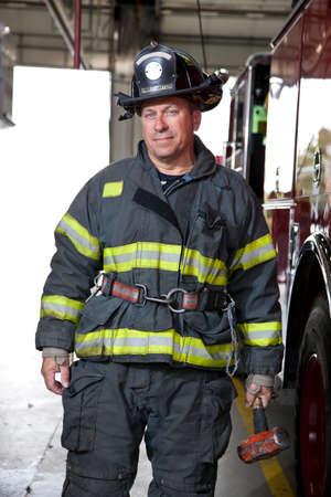 old service station: FireFighter ritratto in piedi di fronte camion dei pompieri