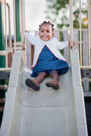 niños jugando en el parque: 3 - año viejo afroamericano chica jugando en la diapositiva en el patio