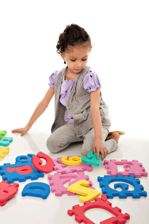early education: Little Hispanic Girl Solving Number Alphabet Puzzle Stock Photo