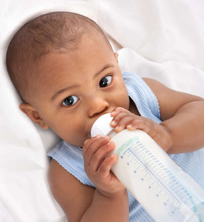 sucking milk: smiling 7-month old baby holding milk bottle lying down Stock Photo