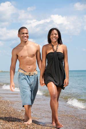 pantalones vaqueros mojados: Dos j�venes tomados de la mano caminar por la playa