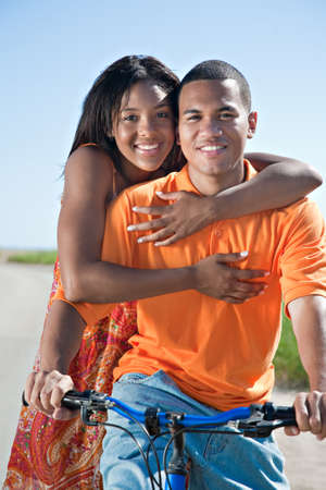 young female: Young African American couple Outdoors Riding Bike Hug Stock Photo