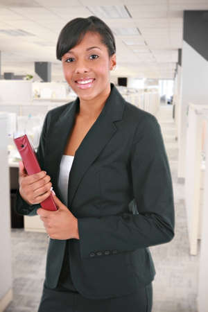 Young Businesswoman Holding Folders Standing in Office Cubes photo