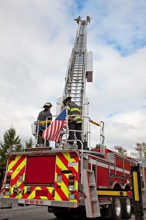 FIRE ENGINE: Deux pompiers opèrent sur le camion d'incendie dans le ciel d'été claires Banque d'images