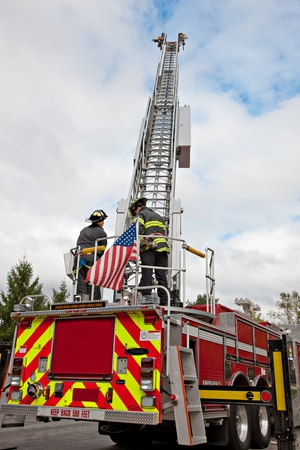 Two Firefighters operate on fire truck in summer clear sky photo