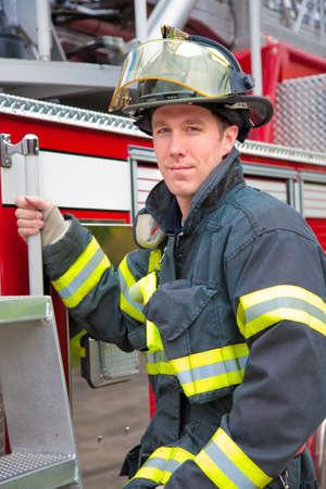 tűzoltó: Fiatal csinos FireFighter előtt álló tűzoltókocsi portré Stock fotó