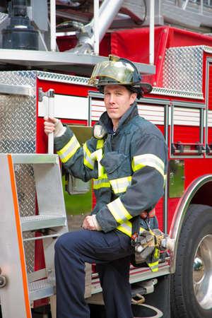 coche de bomberos: Joven apuesto bombero permanente delante retrato de cami�n de bomberos Foto de archivo