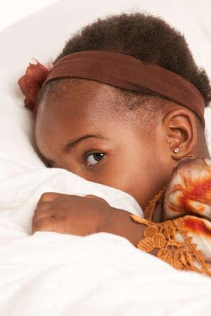 3 year old African American girl in colorful custume playing hide seek photo