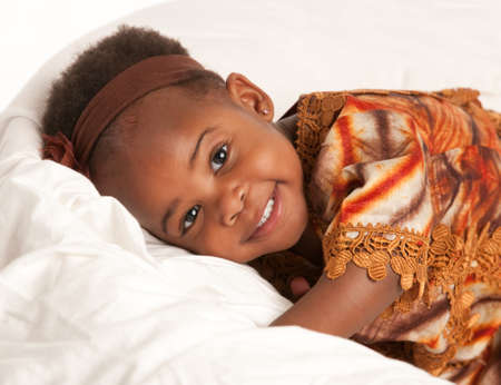 3 year old: 3 year old African American girl in colorful custume sit on bed Stock Photo