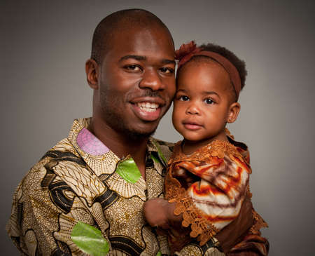 Happy African American Father Holding Baby Girl Portrait Isolated on Grey Background photo