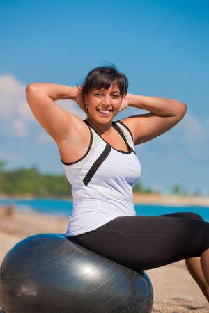 mujeres gordas: Adem�s de tama�o femenina ejercicio exterior en Fitness Ball en frente de agua