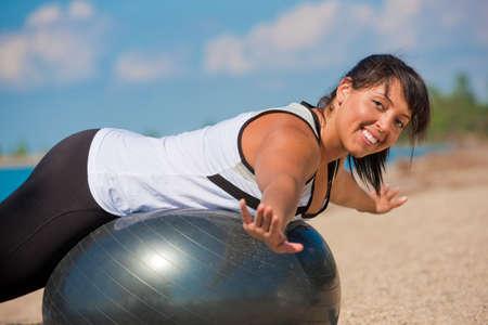 sobre peso: Además de tamaño femenina ejercicio exterior en Fitness Ball en frente de agua