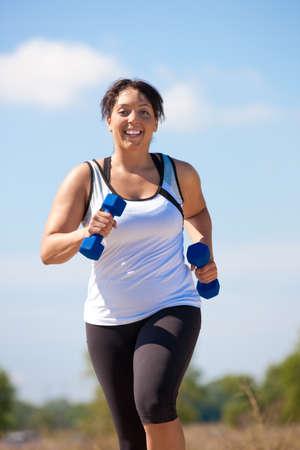 donne obese: Plus Size femminile Sorriso esercizio all'aperto felice sotto Sunny Sky Blu Archivio Fotografico