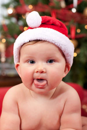 Cute Infant Baby in front of Christmas Tree Wearing Santa Hat Stock Photo - 10764294