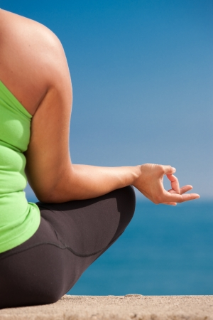 body built: Plus size female practice yoga outdoor under blue sky Stock Photo