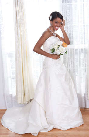 Beautiful Young Bride Standing by Window Smiling photo