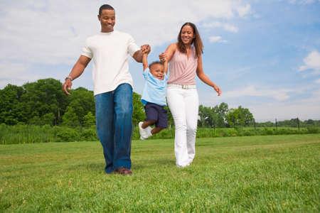 famille africaine: Heureux gar�on souriant Jouer en plein air avec les parents journ�e d'�t� ensoleill�e