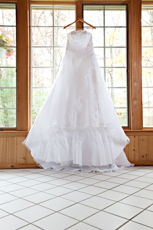 Beautiful White Wedding Gown Hanging by Window