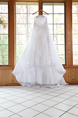 Mooie White Wedding Gown Opknoping door Window Stockfoto
