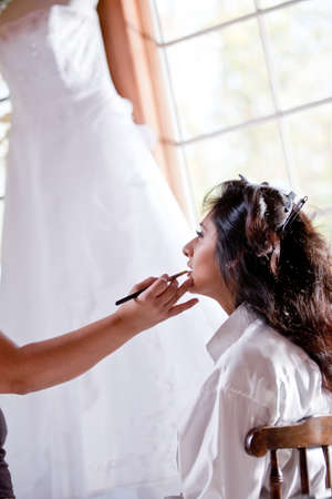 Smiling bride getting ready geting makeup  in front of window with wedding gown hanging photo