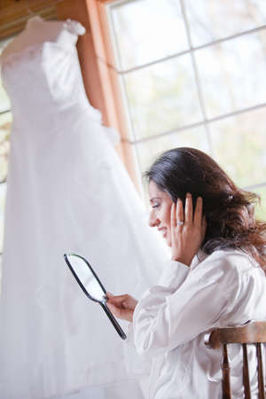 Smiling bride getting ready looking at the mirror in front of window photo