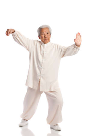taichi: Chinese Elderly Woman Performing Tai Chi Isolated on White Background