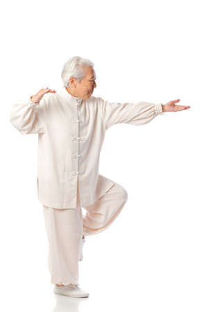 chi: Chinese Elderly Woman Performing Tai Chi Isolated on White Background