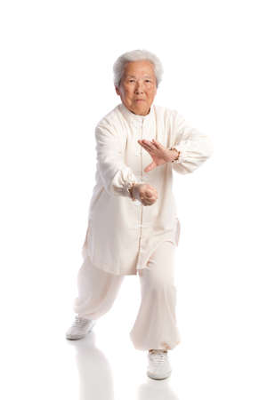 Chinese Elderly Woman Performing Tai Chi Isolated on White Background photo