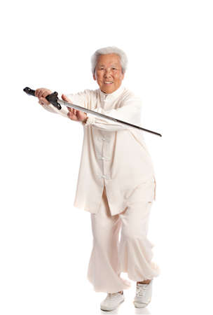 Chinese Elderly Woman Performing Tai Chi with Sword Isolated on White Background photo