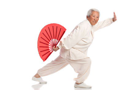 chi: Chinese Elderly Woman Performing Tai Chi with Red Fan Isolated on White Background