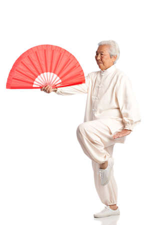 taichi: Chinese Elderly Woman Performing Tai Chi with Red Fan Isolated on White Background