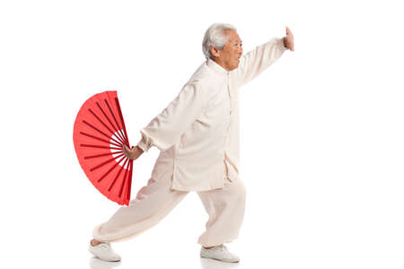 Chinese Elderly Woman Performing Tai Chi with Red Fan Isolated on White Background photo