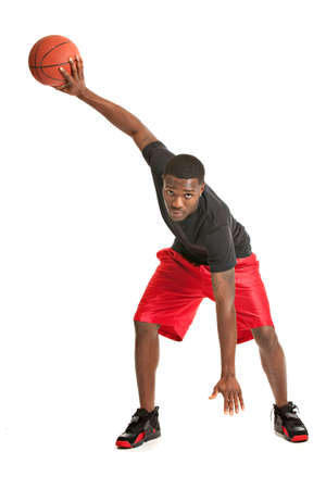 canestro basket: Giovane College Student Nero Giocare Basket Ball su sfondo bianco isolato Archivio Fotografico