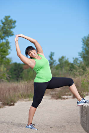 Plus Size Female Exercise Stretch Outdoor Under Sunny Blue Sky photo