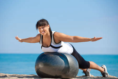plus size: Plus Size Female Exercise Outdoor on Fitness Ball in water front