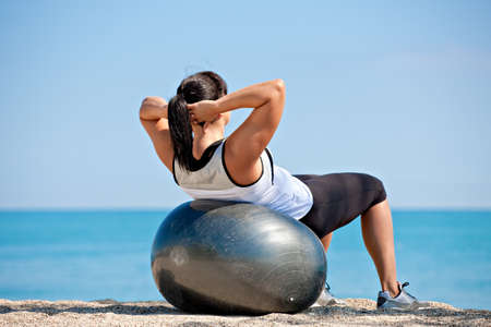 Plus Size Female Exercise Outdoor on Fitness Ball in water front photo