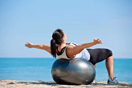 Plus Size Female Exercise Outdoor on Fitness Ball in water front Stock Photo - 13260789