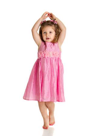 niños bailando: 3 años de edad la niña con vestido de color rosa representan la danza vertical feliz en el fondo blanco