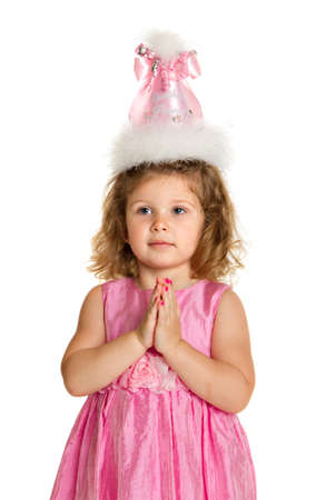 3 year old birthday girl with pink dress and hat make wish isolated on white background photo