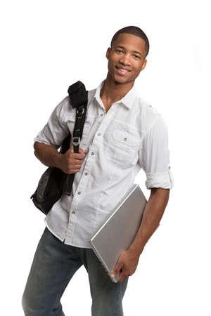 バックパック: 孤立した白い背景の上のラップトップを保持している幸せなアフリカ系アメリカ人大学生 写真素材
