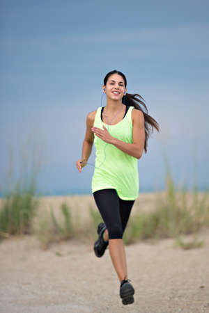Healthy Looking Young Woman Jogging under Morning Blue Sky by Beach photo