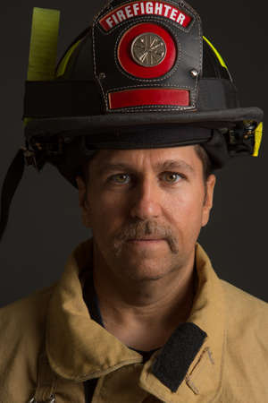 sholders: Serious looking confident firefighter Headshot Portrait on Dark Background