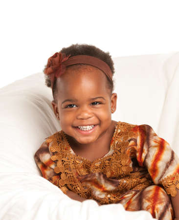 3 year old: 3 year old Smiling  African American girl in Colorful Costume sit on bed Stock Photo