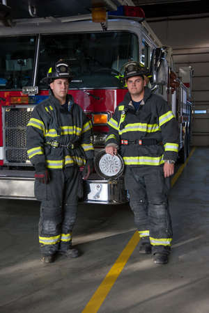 Two Firefighters standing in front fire truck group portrait in fire station photo