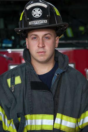 bombero de rojo: Bombero joven de pie en posición vertical frente camión de bomberos Foto de archivo