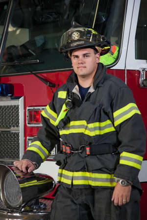 Young Fireman standing in front fire truck portrait photo