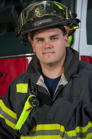 bombero de rojo: Joven Headshot Fireman pie delante retrato camión de bomberos Foto de archivo