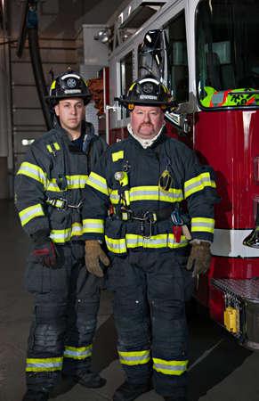 bombero de rojo: Dos bomberos de pie en el retrato de grupo delantero camión de bomberos en la estación de bomberos