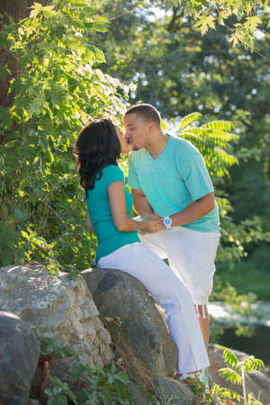 Young Hispanic Couple Engagement Picture Outdoor Portrait Back Lit by River Kissing Each Other photo