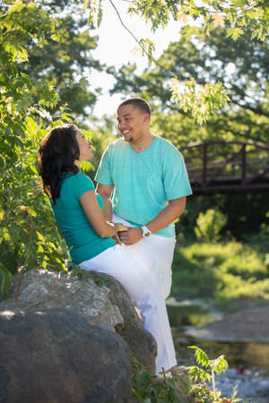 Young Hispanic Couple Engagement Picture Outdoor Portrait Back Lit by River photo